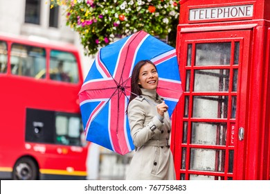 London tourist travel woman with UK flag umbrella, telephone box, red big bus. Europe travel destination Asian girl with british icons, red phonebox, double decker hop on hop off bus in famous city.