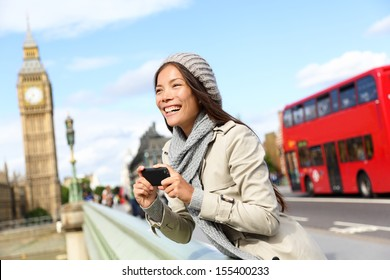 London tourist woman sightseeing taking pictures near Big Ben with red double decker bus. Girl holding smart phone camera smiling happy near Palace of Westminster, Westminster Bridge, London, England