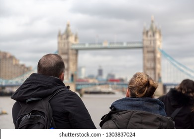London tourists  couple looking at Tower Bridge over the River Thames in central London, England, UK United Kingdom. Visit London concept.