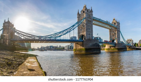 London Tower Bridge panoramic view from Thames river level. Backlight shot of Tower Bridge and the river with cityscape on background. Travel and architecture