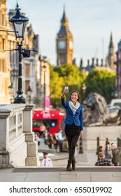 London travel tourist taking selfie picture with mobile phone near Big Ben, UK. Business people at Trafalgar Square, United Kingdom. Europe destination vacation.