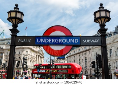 London Tube entrance to public subway at Regent Street, Piccadilly Circus.  Underground logo on foreground and a double decker in background. Sunny summer day. London, UK, 26 May 2016