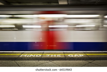 London tube platform edge. Painted warning on the floor. Train passing by.