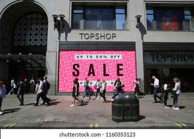 London / UK - 06.22.2018 A sale sign in the window of a fashion shop on Oxford Street in London. With shoppers walking in the foreground