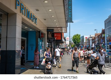 London. UK- 06.26.2020: a busy street scene outside the entrance to Primark with shoppers forming long queues waiting to get in which is the result of social distancing rules for retailers.
