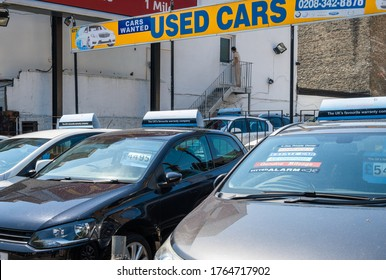 London. UK- 06.26.2020: a used car dealership with cars on display and a sign saying used cars and cars wanted.