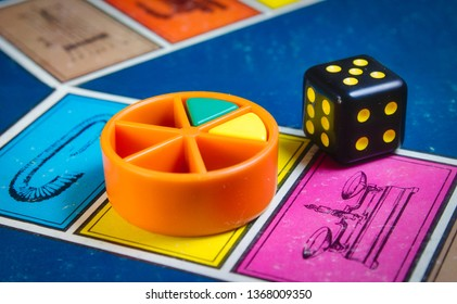 London, UK - 07 April 2019: Close-up of classic board game Trivial Pursuit with black die and colored plastic pieces of different colors