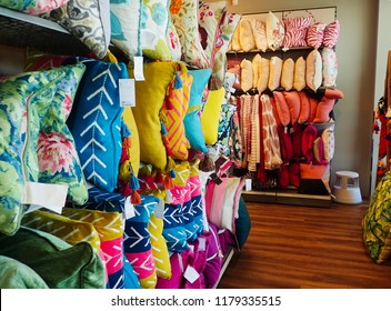 London, UK - 1 August 2018: Cushions and pillows lined up on shelves in a shop.