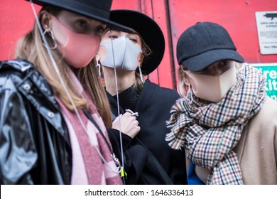 London, UK - 10 February, 2020 People wear mask for protection during fashion week. Three friends in pink and grey masks. Street style.