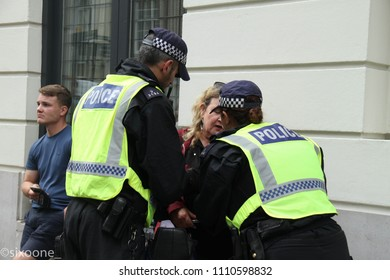London, UK - 10 June 2018: A woman is searched and questioned by police officers during the  demonstration outside the Saudi Arabia Embassy for Al Quds Day.