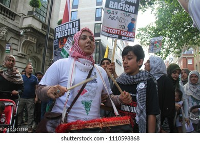 London, UK - 10 June 2018: A female protestor chants  'boycott Israel' as she drums during a demonstration outside the Saudi Arabia Embassy on Al Quds Day.