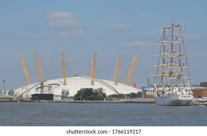 LONDON/ UK- 10th September 2014: The Millenium dome O2 centre, on the banks of the river thames, with a tall sailing ship, docked nearby.