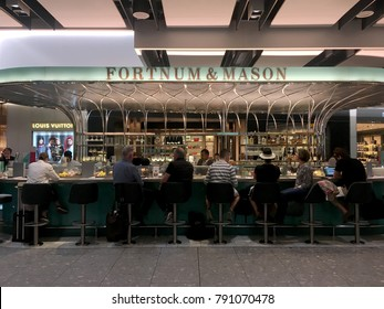 London, UK - 11 August 2017: Two men walk passed people sitting at the bar of Fortnum and Mason, British gourmet luxury retailer, inside Terminal 5 of London Heathrow Airport in London.