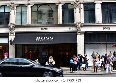 London, UK - 11 August 2019: Crowds of people and black car driving by Hugo Boss store on Regent Street. Hugo Boss, founded in 1924, is a German luxury fashion house headquartered in Metzingen.
