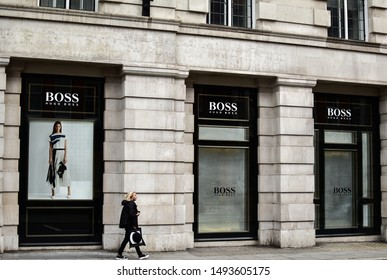 London, UK - 11 August 2019: Woman walking outside of Hugo Boss Store on Sloane Square. Hugo Boss AG is a German luxury fashion house headquartered in Metzingen. It was founded in 1924 by Hugo Boss.