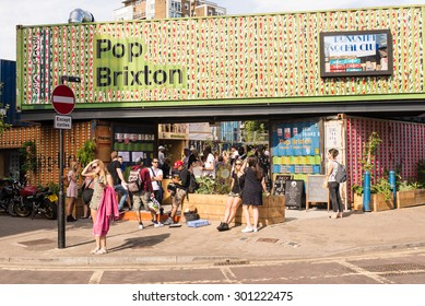"London, UK - 11 July 2015: People enjoying the London summer in a new pop-up opened in Brixton called ""Pop Brixton"". It is a new popular venue with trendy restaurants, cafe and live music."