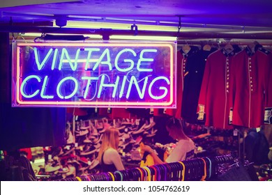 London, UK - 11 March, 2018 - Neon sign VINTAGE CLOTHING with a few customers browsing in the background at Camden market
