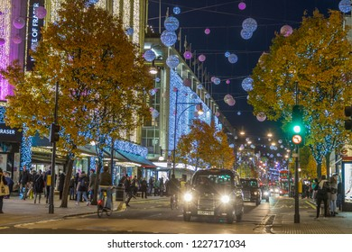 LONDON, UK - 11TH NOVEMBER 2018: Views along Oxford Street with colourful Christmas decorations and lights. Lots of people and a London taxi can be seen.