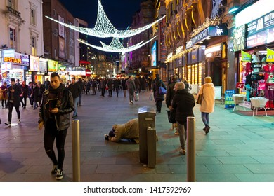 London U.K. 12-17-2018. Homeless person in the middle of Christmas decorated night street.