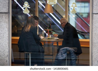 London U.K. 12-17-2018.Old man and young couple siting in cafeteria. View through shop window.