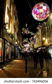 London, UK - 12/29/15: Shoppers under Christmas Decorations on Carnaby Street, photographed from junction with Lowndes Court.