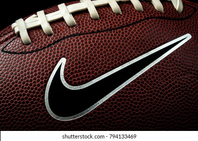 London, UK - 12th January 2018:Illustrative editorial of a macro image of a american football ball with visible laces, stitches, pigskin pattern and the nike logo with dramatic lighting