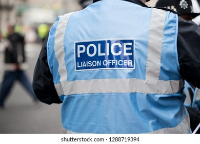 London, UK. 12th January 2019. Police Liaison Officer sign on the back of a blue reflective jacket worn by police officers escorting & monitoring a street demonstration through central London, UK.