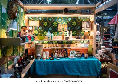 London, UK - 13 February, 2020 Spitalfields flea market. Glass vases and chandeliers in the style of the seventies on the shelves on the background of multi-colored fabric in a green flower