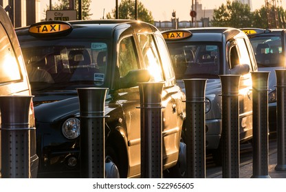 LONDON, UK - 13 MAY 2015: London black taxi cabs at a rank waiting for passengers in the Docklands business district.