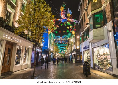 LONDON, UK - 13TH DECEMBER 2017: A view along Carnaby Street in London at night at Christmas. Lots of colorful decorations can be seen.