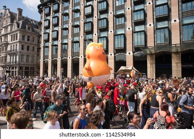 London, UK. 13th July 2018. EDITORIAL - The orange Baby Trump blimp being paraded around Parliament Square, London, UK, at the #BringTheNoise Women's March Anti Donald Trump protest demonstration.