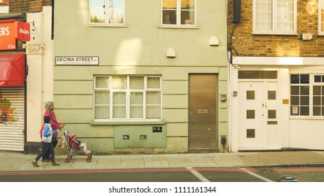 London / UK - 15 04 2016 - Mother pushes a pram with her son in a residential pocket or Southwark SE1 district