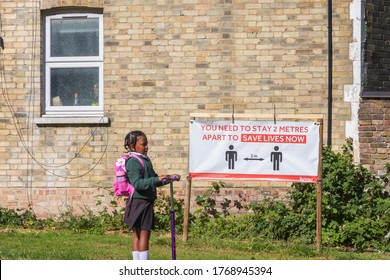 London, UK - 16 June, 2020 - Social distancing sign with an indication of 2 metres distance in a park and a girl riding a scooter through