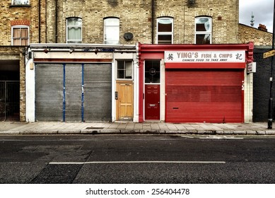 LONDON, UK - 16 SEPTEMBER 2012: Closed businesses.  The closed and shuttered shop front facades in a deprived area of North London.