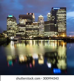 LONDON, UK - 16TH JULY 2015: The outside of Canary Wharf in London at night showing the office buildings and reflections in the water.