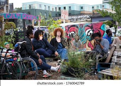 London, UK - 17 July 2019, Nomadic Community Garden. Communal Garden Party. Friends are sitting at tables in a street cafe. Their friend photographs them