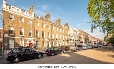 LONDON, UK - 17 MAY 2018: A terraced row of grand Georgian town houses in Bedford Square, Bloomsbury, London, with traffic filling the narrow urban streets.
