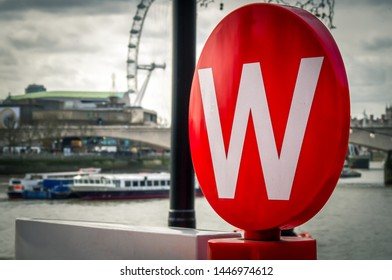 """London, UK / 17-01-22; Street sign of white """"W"""" letter in the red color circle. Sign marks city tour bus stop spot in London. London eye and river Themes is seen in the background."""