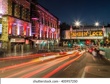 LONDON, UK - 17TH JULY 2015: The outside of buildings and a bridge in Camden Lock at night. The trails of traffic can be seen.
