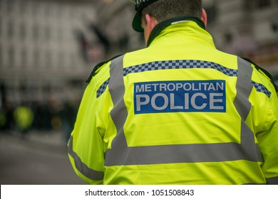 London, UK. 17th March 2018. EDITORIAL - Close up view of Police sign on the back of a Metropolitan Police Officer's yellow reflective jacket as he goes about his duties in central London, UK.