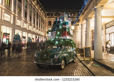 LONDON, UK - 17TH NOVEMBER 2018: A decorated car with presents on top at Covent Garden in London at night. People can be seen.