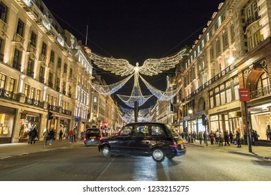 LONDON, UK - 17TH NOVEMBER 2018: Views along Regent Street at night showing Christmas decorations along the street. A typical London Black Cab can be seen going past.