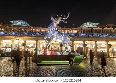 LONDON, UK - 17TH NOVEMBER 2018: A large decorated reindeer at Covent Garden in London at night. People can be seen.