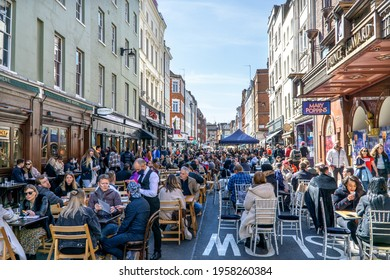 London, UK - 18 April 2021: Lockdown easing, outdoor drinking and dining outside pubs on Old Compton Street, Soho, central London