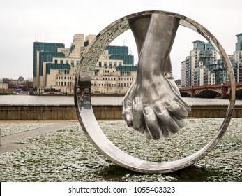 "London U.K. 18 Mar 2018: Lorenzo Quinn's ""Love"" in the snow looking at the MI6 building and Vauxhall Bridge"