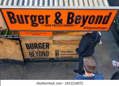London, UK - 18 May, 2019 - A burger stall at Camden market with queuing customers