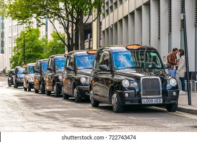 LONDON, UK; 18.04.17: Row of London Taxis lined up along the sidewalk. The London's iconic black cabs are a symbol of the city and a major attraction in themselves.