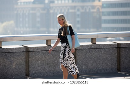 London, UK - 19 April, 2018: Young woman  walking over the London bridge on the way to work in the City of London. Early morning commuters.