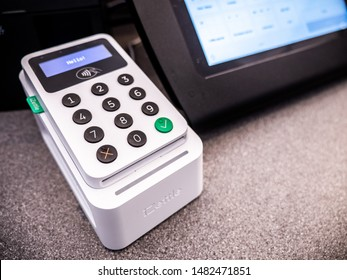 LONDON, UK - 19 JULY 2019: An iZettle POS credit card reading machine on a shop counter with touch screen till in the background.