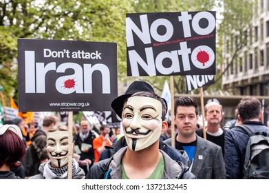 """LONDON, UK - 19 May 2012: protesters hold placards reading 'No to NATO' and ' Don't attack Iran"""" during an anti-war pacifist rally outside the US Embassy in London"""